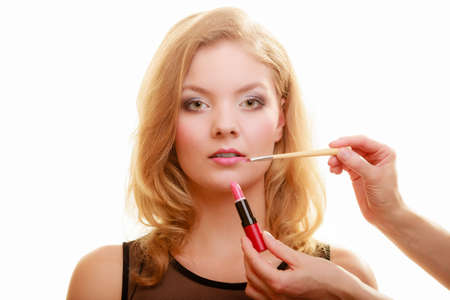 makeover: Cosmetic beauty procedures and makeover concept. Makeup artist applying lipstick with accessories tools to woman lips. Isolated studio shot