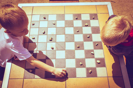 draughts: Draughts board game. Little boys clever children kids playing checkers thinking, outdoor in the park top view. Childhood and development