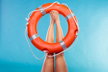 lifebelt: Accident prevention and water rescue. Life buoy ring lifebelt on female legs studio shot blue background