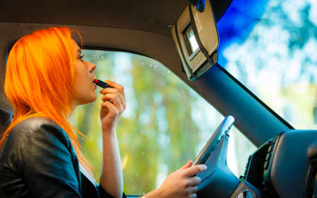 driving: Concept of danger driving. Young woman driver red haired girl painting her lips doing makeup while driving the car.