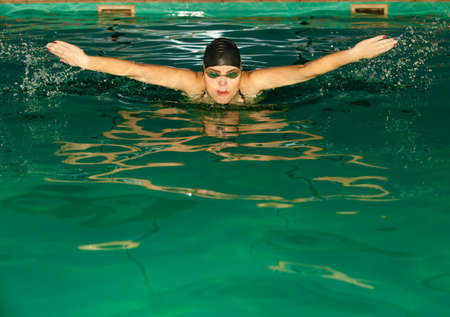 copysapce: Swimming. Competition and recreation. Woman swimmer breathing. Poolside.