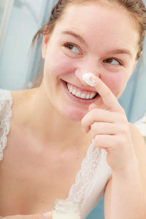 complexion: Happy young woman applying cleansing moisturizing skin cream on face. Girl taking care of dry complexion layering moisturizer. Skincare.