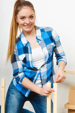 enthusiast: Woman assembling wooden furniture. DIY enthusiast. Young girl doing home improvement.
