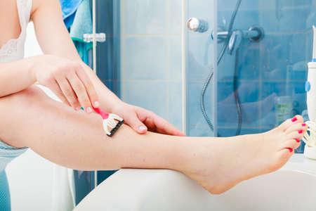 feminist: Hygiene skin body care concept. Hair removal. Closeup woman shaving legs with razor blade in bathroom