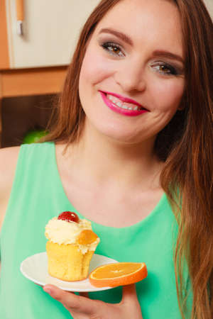 gluttony: Smiling woman holding delicious cake with sweet cream and fruits on top. Appetite and gluttony concept.