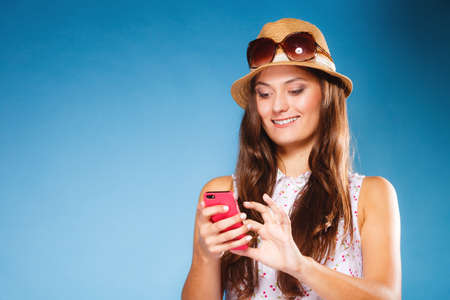 fashionable girl: Technology and internet. Happy woman using cellphone texting on mobile phone. Teen girl reading sms on smartphone, taking selfie on blue