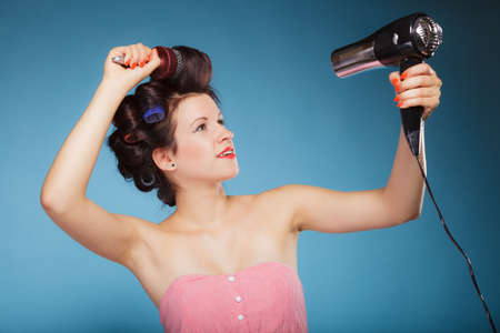 coif: Young woman preparing to party having fun, funny girl styling hair with curlers hairbrush and hairdreyer retro style blue background Stock Photo