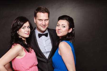 two women and one man: Love triangle or friendship. Portrait of smiling two women and one man wearing elegant clothes on black. Luxury party.