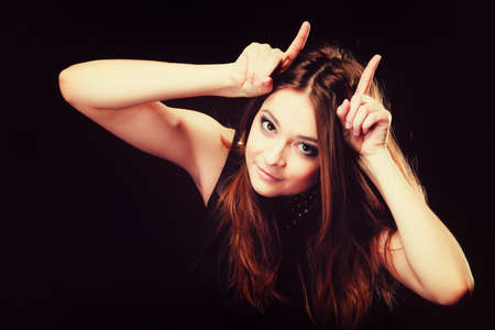 infernal: Funny teen naughty girl making devil horns with her fingers on black Stock Photo
