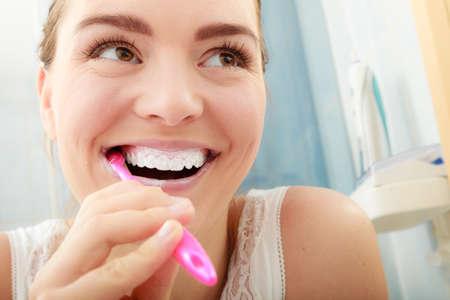 salud: Mujer joven cepillarse los dientes de limpieza. Muchacha con el cepillo de dientes en el baño. Higiene oral. Foto de archivo