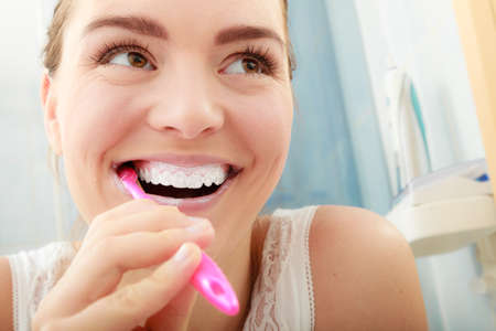 tooth whitening: Young woman brushing cleaning teeth. Girl with toothbrush in bathroom. Oral hygiene.