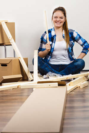 arranging: Woman moving into new apartment house assembling furniture. Young girl arranging interior and unpacking boxes.