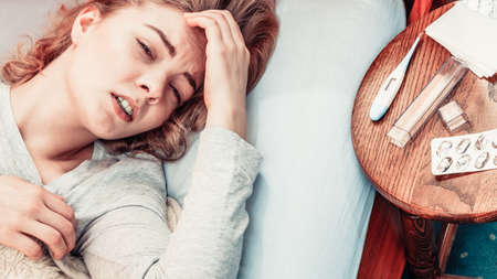 fever: Sick woman suffering from headache pain. Ill girl laying in bed caught cold. Thermometer and pills on table. Stock Photo