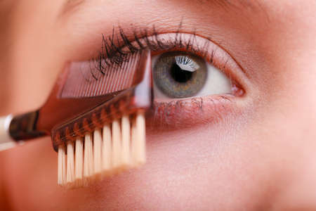 makeover: Cosmetic beauty procedures and makeover concept. Closeup part of woman face eye makeup detail. Using comb to separate lashes after applying mascara, long eyelashes. Stock Photo