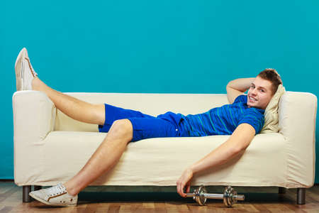 dumb: Relax after sport activity. Young man fit body relaxing on couch, dumb bell on floor