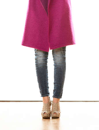 denim trousers: Fashion. Woman legs in denim trousers platform high heels shoes pink coat isolated on white background Stock Photo