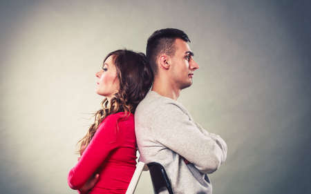 Bad relationship concept. Man and woman in disagreement. Young couple after quarrel sitting on chairs back to back Foto de archivo