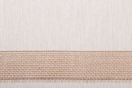 Jute bagging ribbon on bright fabric textile material, natural linen background