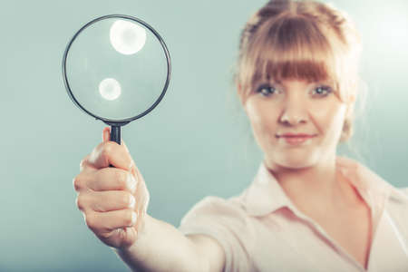 lupa: Investigation exploration education concept. Closeup woman holding magnifying glass loupe in hand filtered photo