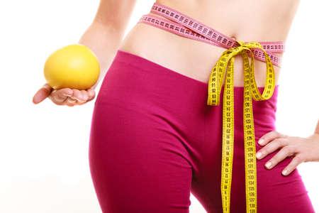 comiendo frutas: Holding humano pomelo medir la cintura con cinta m�trica. Adelgaza y la dieta. Concepto sano estilo de vida de la nutrici�n. Aislado en blanco.