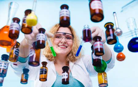 investigando: Experimento, la investigación en curso. Mujer del químico o niña estudiante, auxiliar de laboratorio o investigador científico con química matraz de ensayo de vidrio en azul