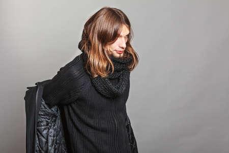 vistiendose: Apuesto hombre de moda vestirse vistiendo abrigo negro y una bufanda. Individuo joven que presenta en estudio. Invierno o la moda de otoño. Foto de archivo