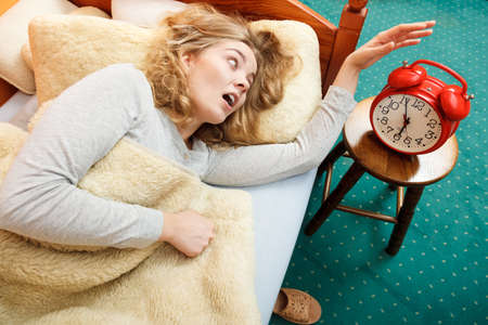 clock: Panic woman waking up late in morning turning off alarm clock. Young girl laying in bed.