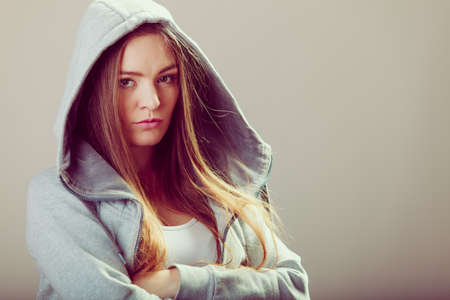 Portrait of rebellious pensive thoughtful teenager crossing arms wearing hooded sweatshirt.