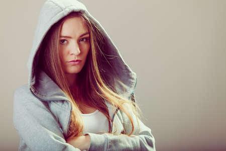 hooded sweatshirt: Portrait of rebellious pensive thoughtful teenager crossing arms wearing hooded sweatshirt.