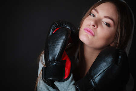 girl kick: Martial arts or self defence concept. Sport boxer woman in gloves. Fitness girl training kick boxing on black background Stock Photo