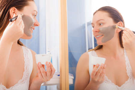 facial: Beauty skin care cosmetics and health concept. Young woman holding brush and bowl with facial clay mask applying mud to her face in bathroom Stock Photo