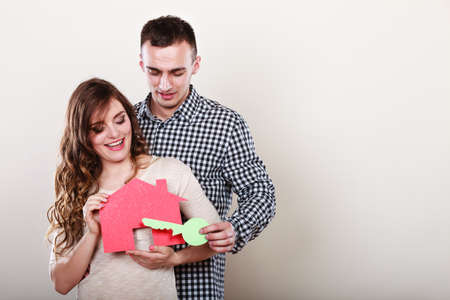 buy house: Smiling young couple holding paper house and key. Husband and wife dreaming about new home. Housing and real estate concept.