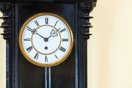 reloj de pendulo: Primer reloj de madera grande y viejo péndulo que cuelga en la pared