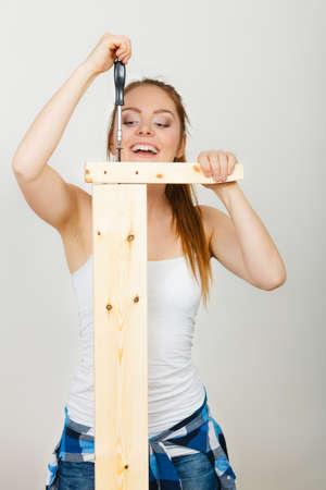 Vrouw die houten meubilair assembleert dat schroevedraaier gebruikt. DIY liefhebber. Jong meisje dat het huisverbetering doet. Stockfoto