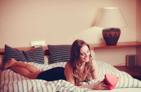 ropa interior femenina: Mujer seductora vistiendo ropa interior en la cama en su casa. Atractiva chica sensual joven con la caja en forma de coraz�n. Moda femenina ropa interior. Valentines d�a.