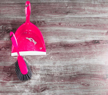 Cleaning and home concept. Sweeping brush small whisk broom and dustpan for house work with garbage on floor indoors.
