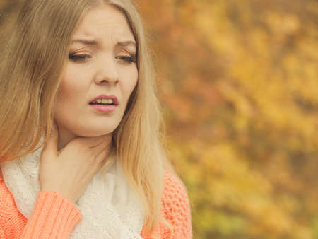 allergy: Sick woman in fall autumn park. Ill girl caught cold flu outdoor. Rhinitis or allergy. Health care.