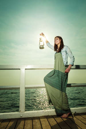 Full length young woman on pier with oil kerosene lamp. Concept carrying light, daylight Stock Photo