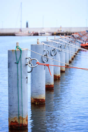 bollards: harbor quayside mooring metal bollards with rope in marina outdoor Stock Photo