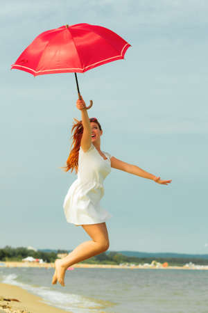 beach umbrella: Holidays, vacation travel and freedom concept. Beautiful redhaired happy girl jumping with red umbrella on beach.
