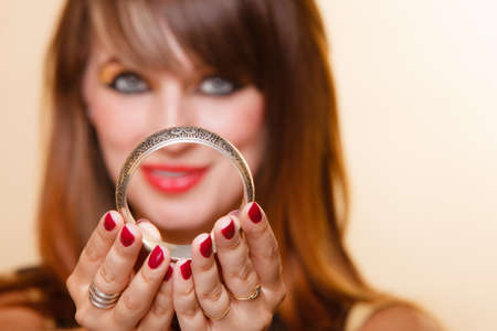 armlet: Closeup young orient eastern girl with makeup. Woman showing jewelry fashionable accessories bijouterie armlet. Manicure red nails. Stock Photo