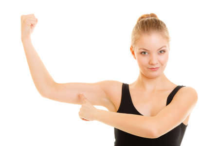 sportwear: trength and power concept. Fitness woman showing fresh energy flexing biceps muscles. Girl in sportwear energetic and fun isolated Stock Photo