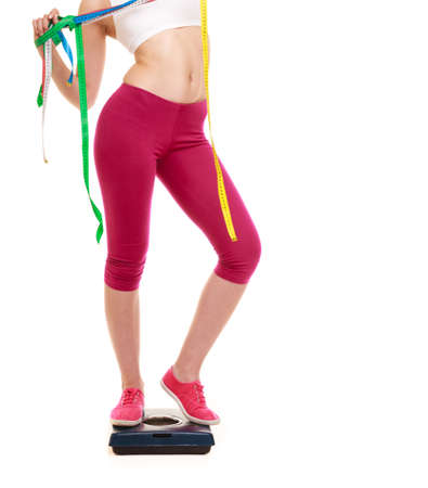 measures: Slimming and weight loss. Woman girl holding tape measures on weighing scale. Healthy lifestyle concept. Isolated on white.