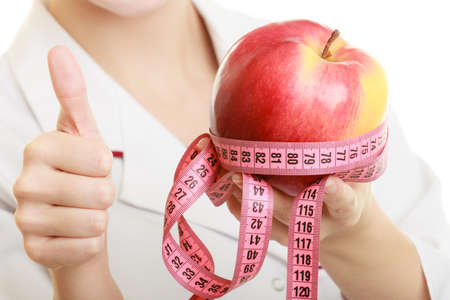 job loss: Slim down dieting concept. woman in white lab coat recommending healthy food. Doctor specialist dietitian holding fruit apple and measure tape isolated.