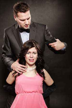 man holding gun: Scene of violence with firearm between men and women. Elegant man holding gun against sitting lady on black and grey background in studio. Stock Photo
