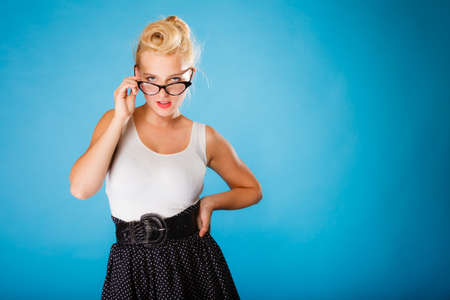 oculist: Optometrist, oculist and ophthalmologist concept. Young blonde retro pin up sexy woman with eyeglasses on blue background in studio. Stock Photo