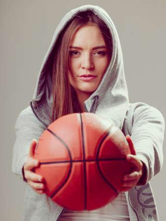sweatshirt: Sporty teenager girl wearing hooded sweatshirt holding basketball. Teen sport.