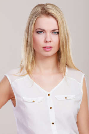 frowned: Woman frowning and looking askance. Attractive blonde girl thinking on gray background
