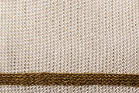 bagging: Jute bagging ribbon on bright textile material, sack cloth background Stock Photo