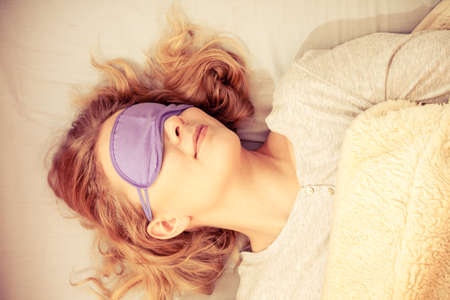 sleep mask: Tired woman sleeping in bed wearing blindfold sleep mask. Young girl taking nap. Instagram filtered.